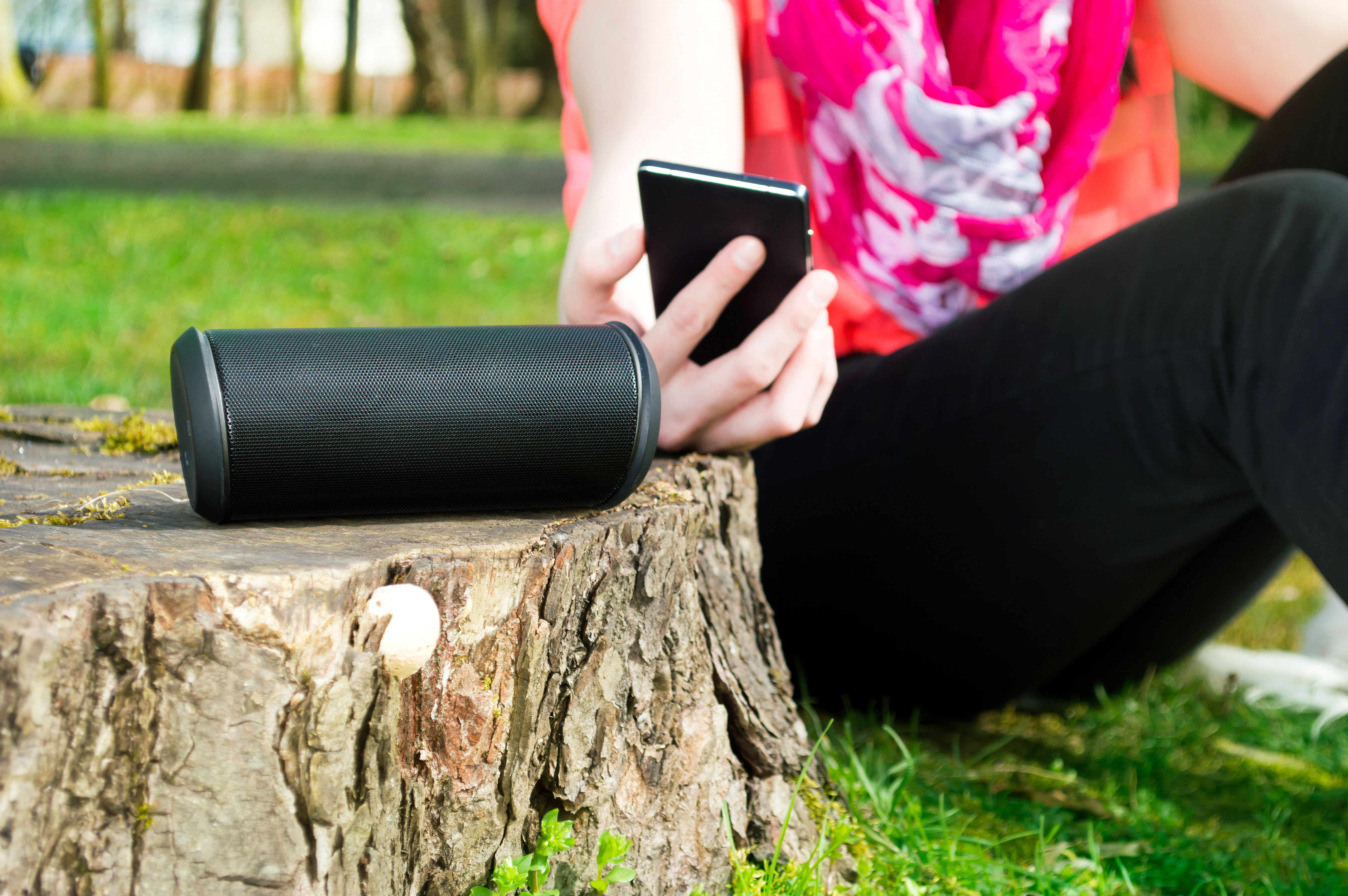 Woman is connecting her smartphone with wireless speaker while being outdoor.
